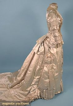 "TRAINED IVORY SATIN WEDDING GOWN, 1880s - 2 piece: front lacing bodice trimmed w/ Brussels lace, shirring on bodice center front, sleeves, & on skirt center-front, skirt w/ outside pocket & long train, t/w 1 wax orange blossom headpiece, B 34"", W 24"", Front Skirt L 42"", Back L 78"", DLM(minor underarm stains) excellent."
