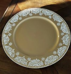 Gold charger plate with hand painted henna design in white.