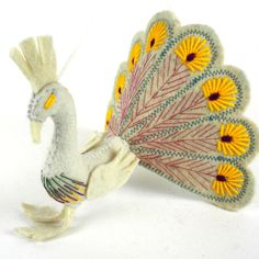 Women in Kyrgyzstan made this stunning peacock ornament by hand from felt. With a loop for hanging and embroidered accents, the ornament's tail measures 8 inches across with a 5-inch tall bird. Meet t
