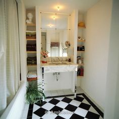 Ambience Images | Underset basin in marble unit below mirrored wall tiles in bathroom black and white chequerboard ceramic floor tiles