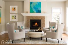 """In the family room, four wing chairs from Room & Board and a Kravet ottoman center around the herringbone-pattern tiled fireplace to anchor the seating area. To the left of the fireplace are two abstracts by Denver artist Mary Mackie; showcased above the mantel is Leslie Gifford's """"Blue, Green and a Touch of Yellow,"""" from Whitney Evans."""