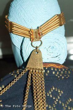 "Chains dangle from a large ""Pakarin,a"" at the back of the headband./ Kārļu Ainavu 4. kapa vainaga rekonstrukcija, skats no aizmugures. 12. gs. (Latgaļi)"