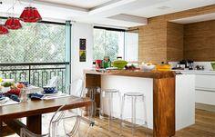 Uma ilha de trabalho foi construída para abrigar o cooktop, já que os moradores usam o espaço para cozinhar. O balcão de madeira é de Monica Cintra.