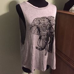 Just in, grey elephant muscle tank Summer is coming and this muscle tank will make a great addition to your closet! Beautiful printed elephant, open sides, and shredded back. Make a statement this season! Only 6 available, so don't miss out. Poly/spandex/nylon blend. Hand wash and hang dry suggested. Stargazer Tops Muscle Tees