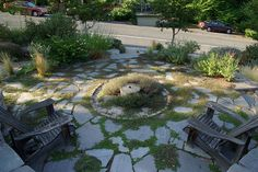 Seattle xeriscaped front yard garden. I like the flagstone with moss, not so sure about the little circly-thingie in the middle.