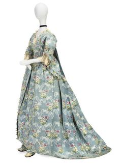 Christie'sAN SACK-BACK OPEN ROBE WITH PETTICOATS, CIRCA 1760S the azure blue silk woven with a polychrome floral bouquet and ribbon motif, the robe with ruched trim and flybraid detail, the sleeves with exaggerated deep ruffle, with matching petticoat