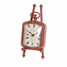 "Weathered metal table clock in red with Roman numerals. Product: Table clockConstruction Material: Metal and glassColor: Red Features: Weathered finish  Accommodates: (2) AA batteries - not includedDimensions: 8.5"" H x 3.75"" W x 5.25"" D"