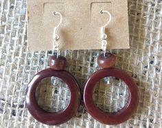 TAGUA NUT AND ACAI SEED DANGLE AND DROP BROWN EARRINGS  These beautiful Brown Tagua earrings are made of round Tagua beads and acai seeds, they have been dyed with organic ingredients only. Tagua, is a nut that grows in Ecuador, and is carved by hand by local artisans. Tagua is also known as vegetable Ivory, because of its resemblance with animal Ivory.  Although chunky, you will find these dangling earrings light and fun to wear, they are very resistant. They will look specially great when…