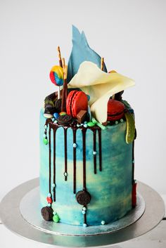 candy cake. Alternating layers of vanilla and chocolate cake with oreo buttercream, chocolate ganache, chocolate sails, macarons, topped with an assortment of candy and sweet treats. www.thelifeharvest.com