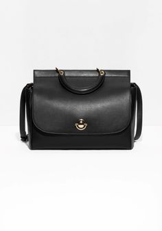 Luxe leather bag with a smooth, matt finish, featuring a unique lock clasp to close flap over bag,