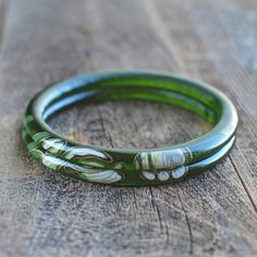 Two green glass bangles handcrafted from a Perrier-Jouët Champagne bottle. These bracelets feature flower graphics from the Belle Epoque bottle.  ** The