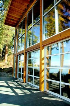 Clopay Avante Collection aluminum and glass panel garage doors open up the view from this lake house family room. Installed by Kitsap Garage Door Co in Bremeron, Washington.