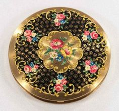 Front of c1950s compact with flowers and scrollwork
