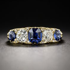 From turn-of-the-twentieth-century Great Britain, a superb, classic 'carved' ring rendered in glorious blue and white and (18K) gold. A trio of natural no-heat sapphires (the center stone is of Cambodian origin, the side stones are Burmese) are interposed by a pair of bright white old mine-cut diamonds and eight tiny rose-cut diamond twinklers, all of which sparkle and radiate from a beautifully sculpted band ring traditionally ornamented with graceful scroll motifs. A timeless Victorian…