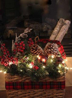 a basket with evergreens, berries, pinecones and lights