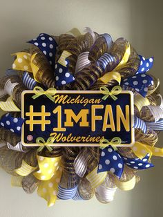 This wreath is made on a royal blue and yellow striped mesh. It features a Michigan Wolverines #1 Fan centerpiece surrounded by lots and lots of blue, yellow and white wired ribbons. What a great way to show your support for your favorite team and to welcome your family and friends to your home. This wreath measures approximately 23 inches in diameter.