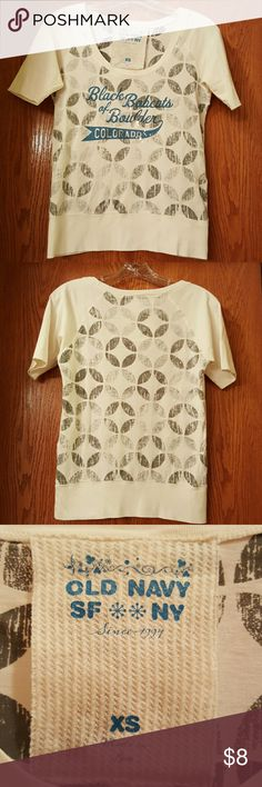 Scoop Neck Graphic T Jersey Style Wide Banding Super cute graphic T. Actually quite white, the camera is giving it a cream cast to the color. Repeating pattern on front and back. Not something you see often with t's. Gives it extra flair! Silver paint spatter for a casual look. Wear with a light gray tank if neck line is too low for your taste. Old Navy Tops Tees - Short Sleeve