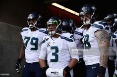 Garry Gilliam #79, Russell Wilson #3, and Justin Britt #68 of the Seattle Seahawks get ready to run on to the field for their game against the San Francisco 49ers at Levi's Stadium on January 1, 2017 in Santa Clara, California.