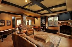 Like the colors, stone accents, beams, not a fan of the TV over the fireplace, not a natural viewing position.