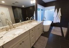 photo of en suite with double vanity built of white shaker cabinets with drawer base separating sinks and undermount sinks, high faucets and marble counter. Bath has large black tiles in floor and shower and tub wall, curbless shower and soaking tub. his and her white terry robes hand in the dry-off area