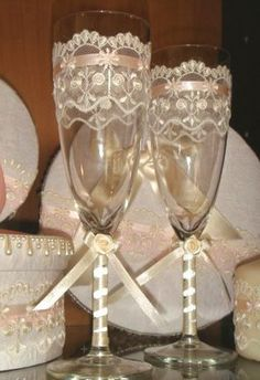 Decoration of wedding glasses with lace and rose from the tapes