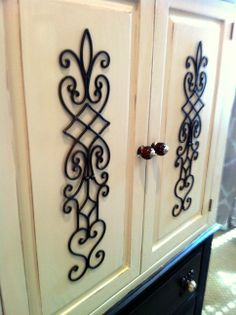 """Two black candle sconces from Hobby Lobby made to look like rustic iron as embellishment to an armoire.  How to:  use bolt cutters to remove the candle holder, spray paint all over with copper paint.  When dry, """"blotch spray"""" lightly with oil-rubbed bronze spray paint.  Then attach to door fronts with tiny little nails (or bolts) that are painted dark brown or black (so they don't show).  Looks amazing."""