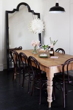 Chic dining room with black arched floor mirror at the end of the space reflecting the black enamel pendant hung over a rustic farmhouse dining table lined with Thonet Bentwood chairs atop black hardwood floors.