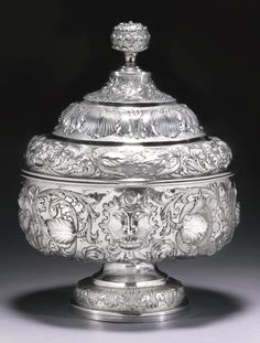 A Portuguese silver bowl and cover, maker's mark MF (Almeida no. L-415) conjoined, Lisbon,  late 17th century  the circular bowl on spreading foot boldly embossed and chased with masks, flowers and scrolling foliage, stepped domed cover similarly decorated and incorporating fruit, bud finial