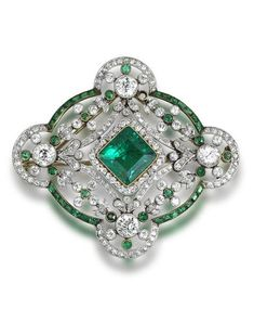 A belle époque emerald and diamond brooch/pendant, circa 1910. Set to the centre with a square-cut emerald and single-cut diamond cluster, to an openwork border set with swags and floral garlands, within a quatrefoil frame, millegrain-set throughout with single and brilliant-cut diamonds and calibré and circular-cut emeralds, diamonds approximately 4.80 carats total, detachable brooch fitting. #EdwardianEmerald