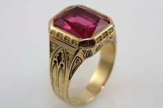 This magnificent men's ring is set with a large rectangular cut created ruby.  The ruby is approximately 11 carats and is in extremely good condition.  The 14K yellow gold setting is meticulously detailed, substantial in weight and finely finished.    Larter & Sons is one of America's oldest and finest jewelry manufacturers.  Founded in 1865, the firm became known for their exquisite line of finely crafted men's jewelry.   Experiments in producing synthetic rubies began in...