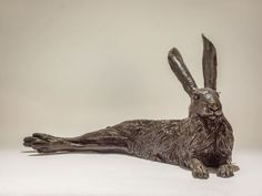 Bronze resin #sculpture by #sculptor Nick Mackman titled: 'Lying Hare (Sitting Lying Resting Hare figurines)'. #NickMackman