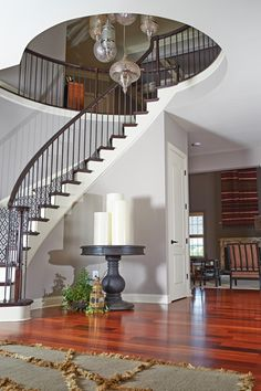 Oversized candles on a contrasting table, Eastern influenced pendant lighting, striking wood floors, a spiral staircase and decorative wool rug create an exciting entry point to this home demonstrating how the foyer – a most often forgotten home component – can create a great first impression.