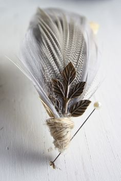 ATHENA SERIES Boutonniere by Pomp And Plumage on Etsy | A lovely crisp boutonniere, the Autumn Solstice is the perfect piece for a fall or winter wedding. It is handmade from a lush grey goose feather, a variegated silver and white plume, and a contrasting champagne tail feather, tied together with rustic twine and an antiqued brass leaf.
