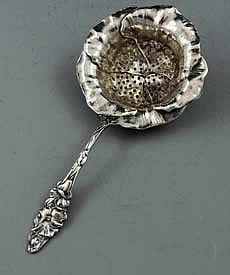 "Watson Sterling Art Nouveau Tea Strainer    A sterling silver tea strainer by Watson with a large floral bowl and ornate handle.    Length: 6 1/2""    Circa 1900"