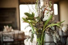 florals with birch branches, seasonal greenery, dusty miller, blue privet berries, and white stock flowers.