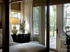 This master bedroom suite features a wood canopy bed, custom window treatments and a glass door onto a bedroom deck bringing the same atmosphere as a retreat.
