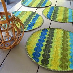 """Add some color and fun to your summer table with this set of four, round Marimekko placemats. The """"Rasymatto"""" print was inspired by the look of rag rugs made from fabric scraps, with rows of dots in avocado green, citron yellow, aquamarine, teal and blue. Machine quilting in intersecting wavy lines highlights each row of dots. Marimekko """"Sade"""" is used to back the placemats."""