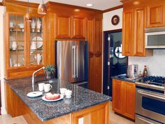 Rich wood cabinetry, granite countertops and stainless appliances round out this traditional kitchen design. Grass-front cabinets allow for the artful display of white dishes and serving pieces.