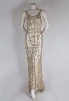 Sequined net evening dress, 1930s. This is the slinkiest, sexiest mermaid dress I have ever seen. With its seductive cut, the sylphlike dress is reminiscent of glamorous 1930s styles. Made from stretchy ivory net, the dress is completely covered with scalloped rows of iridescent sequins. It provocatively molds to the body, ending with a scalloped hem and small back train.