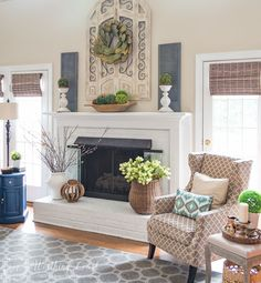This fireplace celebrates the arrival of spring by filling the mantel and hearth with texture and a mix of real and faux branches and greenery. From a basket overflowing with tulips to an urn filled with pussy willow branches, to a magnolia leaf wreath to an abundance of boxwood orbs, there's no doubt what season it is in this family room. Mantel Ideas, Mantles Decor, Fireplace Mantel Decorations, Mantle Greenery, Willow Branches, Vase With Branches, Fireplace Hearth Decor, Fireplace Candle Holder, White Fireplace Mantels