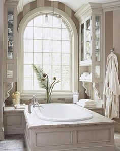 White Bathroom & Bathtub Faces the Window - This tub was purposefully placed facing the window so the homeowner could soak & enjoy the view. Intricate moldings, corbels, & hand-rubbed painted finishes give this bath the look of a classic English manor.