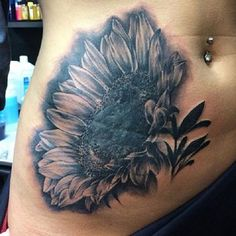 A truly beautiful close up tattoo of a sunflower. You can clearly see each petal of the sunflower drawn in wonderful fashion. A unique and eye catching tattoo design.