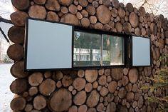 Voor een normale blokhut worden de buitenmuren gevormd door in de lengte gestapelde boomstammen. Piet Hein Eek, belast met de bouw van een gezellige opname