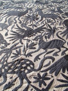 Tenangos are hand made (hand embroidered) by the Otomi Indians from Hidalgo, Mexico. It is said the designs have been inspired from the ancient cliff paintings in the region. 6x6' coverlet available from the Loaded Trunk. via houzz