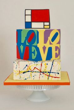 This cake is very bold and different. The couple wanted something inspired by their love of modenrn art for their wedding. The bottom tier is inspired by Jackson Pollock, the middle was inspired by Robert Indiana, and the top tier was inspired by Piet Mondrian. The middle tier is different on all 4 sides, making this cake unique from any angle!