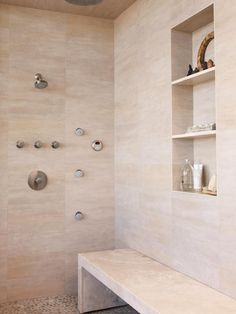 Simple luxury describes this large, open shower with cream and beige marble wall tile and inlaid stone medallion flooring. The built-in shelves and bench are attractive and functional additions to the space.
