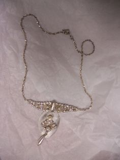 Deconstructed vintage necklace on vintage silver spoon.