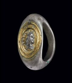 A ROMAN SILVER AND GOLD FINGER RING   CIRCA 2ND CENTURY A.D.   The solid hoop flat on the interior, rounded on the exterior, expanding to the broad angular shoulders, the bezel centered by a relief radiate bust of Helios in profile to the right, framed by raised bands, the bezel overlaid in sheet gold, the face and hair of Helios cut out to reveal the silver below