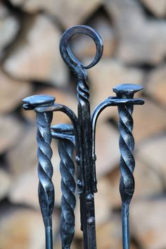 This fire iron set is hand forged out of iron and railroad spikes. The set consists of a stand and three fire tools: a shovel, poker and brush.