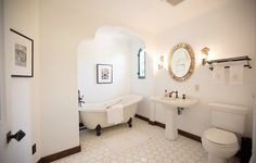 Large hexagonal tiles cover the floor of an all-white bathroom, where a clawfoot bathtub takes center stage.